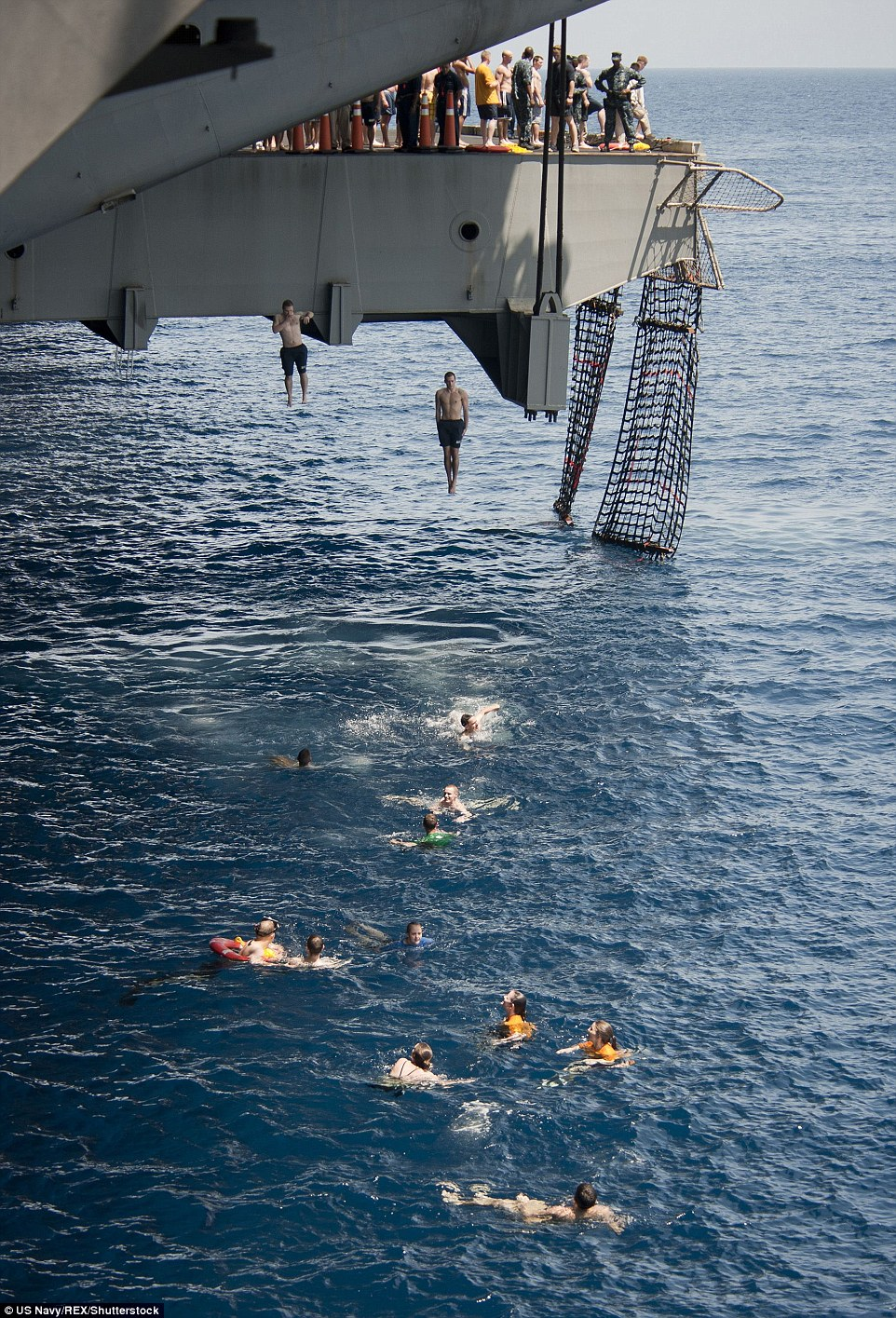 Pencil jump:Sailors leap into the Arabian Sea from an aircraft elevator during a 'swim call' aboard the Nimitz-class aircraft carrier USS Carl Vinson (CVN 70)