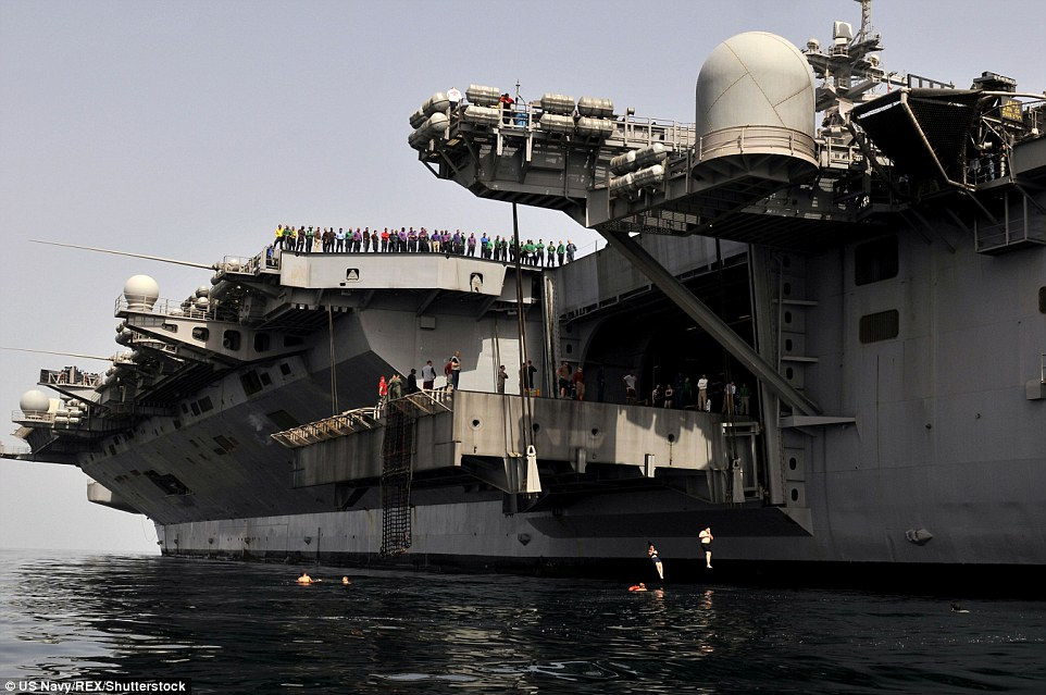 Look out: People watch from ships and from rigid-hulled inflatable boats on the USS Carl Vinson in the Arabian Sea to make sure no sharks become intrigued by sailors swimming