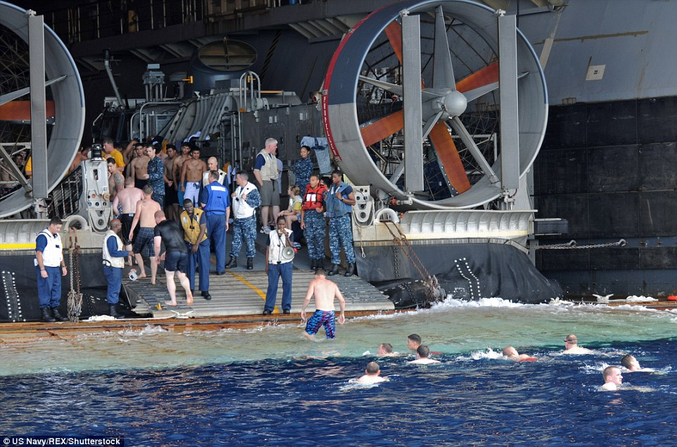 Enough for one day: Sailors return to the multi-purpose amphibious assault ship USS Essex after having a swim in the Celebes Sea