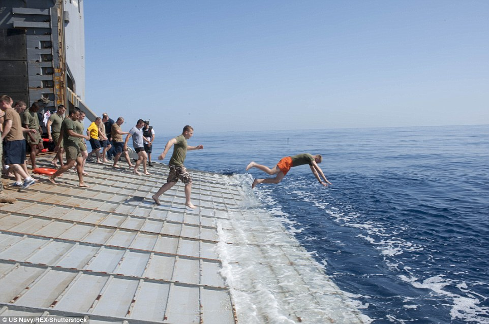 Taking the plunge: Sailors and Marines aboard the amphibious dock landing ship USS Fort McHenry (LSD 43) jump off the stern gate