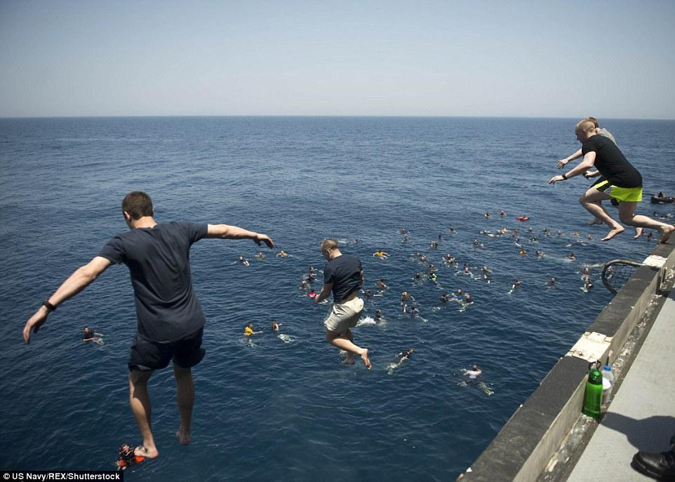 Giant leap: Sailors jump into the Arabian Sea from an aircraft elevator during a 'swim call' aboard the aircraft carrier USS Dwight D. Eisenhower (CVN 69)