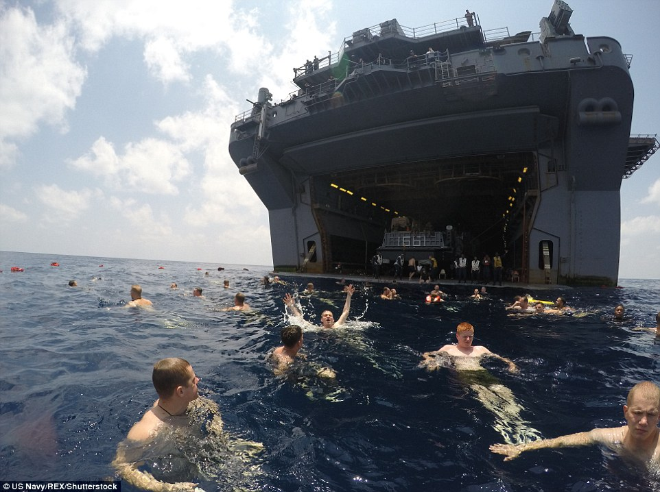 Hands up: The US Navy have fun together while swimming and cooling off in the warm weather in the Gulf of Aden in the Arabian Sea; here sailors and Marines aboard the assault ship USS Iwo Jima cool off in the Gulf of Aden