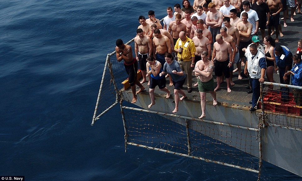 Wait your turn! Dozens of Marines line up to jump off the portside aircraft elevator during a swim call aboard the amphibious assault ship USS Tarawa back in 2008