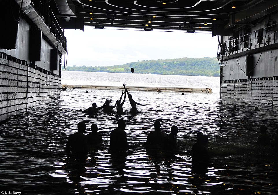 Play ball: Sailors play football during a swim call in the well deck of the amphibious transport dock ship USS Cleveland back in 2011