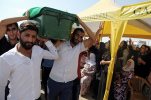 People carry a victim's coffin as they attend funeral services for dozens of people killed in last night's bomb attack targeting an outdoor wedding party in Gaziantep, southeastern Turkey, Sunday, Aug. 21, 2016. The suicide attacker was an Islamic State group child as young as 12 years old. The extremist group has a history of using children as weapons, sending them to their death strapped with explosives and putting them on front lines in Iraq and Syria. (AP Photo/Mahmut Bozarslan)
