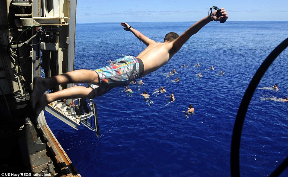 Incoming:The spectacular snaps show sailors and marines partaking in an activity known as a 'swim call' around the world; In this particular image, a sailor jumps off the San Antonio-class amphibious transport dock ship USS Mesa Verde in the Mediterranean