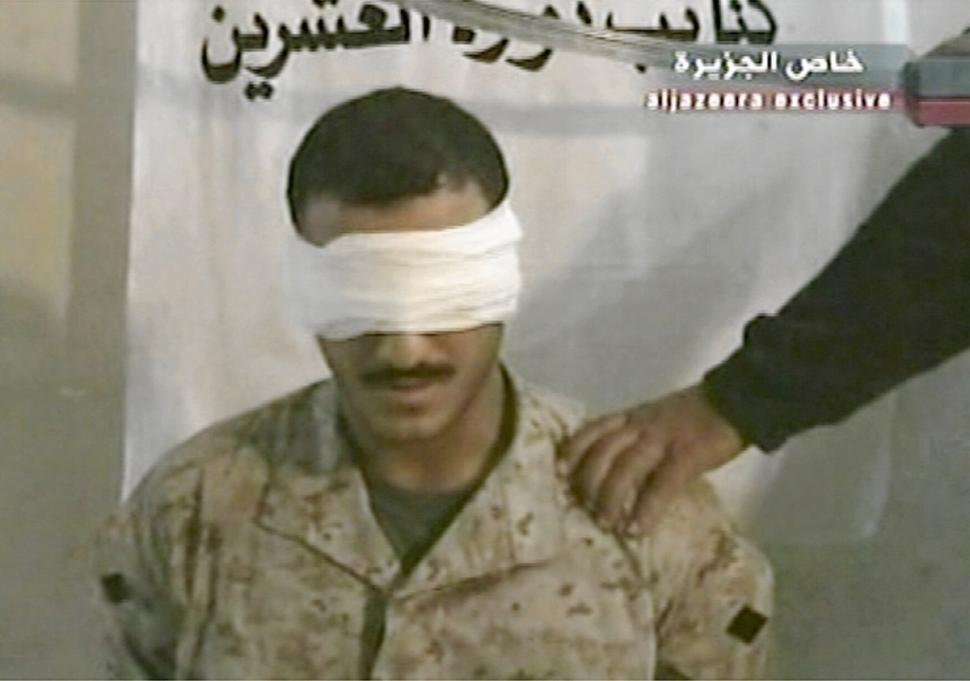 A television image aired by Al Jazeera on June 27, 2004 shows a blindfolded man dressed in camouflage and identified as Wassef Ali Hassoun sitting in a chair with a hand holding a sword above his head. The Lebanese-born U.S. marine is alive and free after having been thought to have been decapitated by his captors in Iraq, the hostage's brother said July 6, 2004.